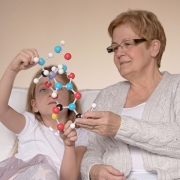 A woman and a child examine a DNA molecule